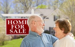 Senior Couple Front of For Sale Real Estate Sign and House.